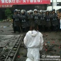 A protester kneels in front of oncoming riot police during the Shifang demonstrations against a copper refinery. By Shi Fengrong, via Tea Leaf Nation.