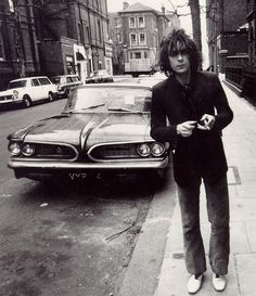 Syd Barrett originally of PInk Floyd photographed by Mick Rock next to an American car, presumably in London around 1967 or 68. I loved the first Pink Floyd album Piper at the Gates of Dawn. I love the casual nature of this photo