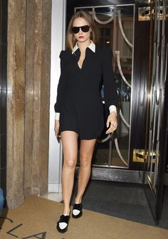 Cara Delevingne wears a black and white tuxedo dress with Jimmy Choo spectator oxfords
