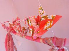 Perchoir rose à oiseaux par Estampapier. 2 kotobizurus et 2 grues rose en papier washi, sont entourés de bandes de tissus dans les mêmes tons. Prix: 12€