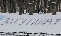 """Feb 2012: People walk in a park with sign """"For Putin"""" written on snow in downtown St Petersburg, Russia. Tens of thousands of people demonstrated in support of Prime Minister Vladimir Putin in cities across Russia."""