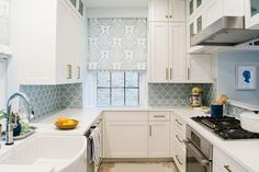 U-shaped white and blue kitchen boasts white shaker cabinets finished with satin brass pulls accented by a blue fish scale tile backsplash highlighting windows covered in white and blue roman shades in Galbraith & Paul Lotus fabric.