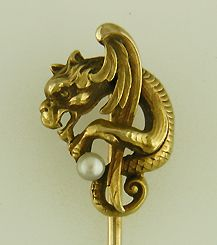 A winged serpent warily clutches a small pearl.  This little fellow has a lot of charm. The perfect miniature gargoyle to keep demons and goblins from your lapel.  Beautifully crafted in 14kt gold,  circa 1900.