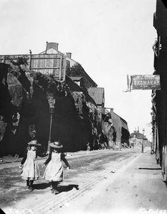 Två flickor befinner sig vid hörnet av Renstiernas Gata och Åsögatan österut. Berget ska sprängas bort för breddning av Renstiernas Gata och Åsögatan. Husen på höjden ligger vid Beckbrännargränd - Stockholmskällan
