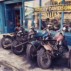 A whole row of vintage Harley's outside of a vintage looking Harley Davidson dealership