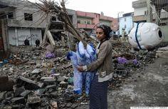 ガレキの山になったトルコの街。政府軍とクルド人武装勢力の戦闘が激化/// シロピの家の廃墟から寝具を取り出ている女性。1月下旬、部分的に解除されるまで、この都市は36日間にわたって終日、外出禁止令の下にあった。