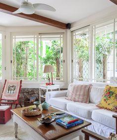 Sala de estar iluminada tem parede de pedra, sofá branco e poltrona de fibra.