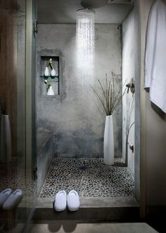 Gorgeous industrial bathroom with pebble floors, an oversized shower head, glass door and gray walls | Melissa Winn Interiors