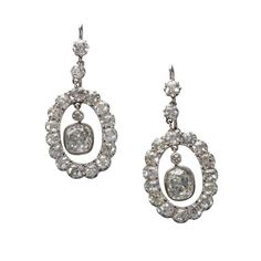 A pair of diamond and platinum pendant earrings <br /> each suspending an old cushion shape diamond, weighing approximately 1.40 and 1.30 carats, surrounded by old mine-cut diamonds; estimated total remaining diamond weight: 3.50 carats. <br />