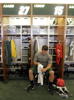 New York Jets quarterback Tim Tebow sits at his locker at the teams training center, Thursday, May 10, 2012 in Florham Park, N.J.