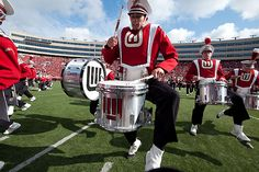The drum line high steps at halftime at Camp Randall.
