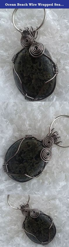 Ocean Beach Wire Wrapped Sea Stone Key Chain. The stone used in this one-of-a-kind key chain originates from a beach in Western Newfoundland, Canada. Chosen for its black and green dappled coloring, this piece has been hand wrapped in stainless steel wire with double swirl accent and attached to a key ring.