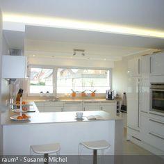 Offener Küchenbereich mit Esstresen und indirekter Beleuchtung