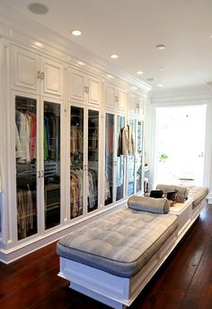 CLOSET with glass doors and tufted bench seating