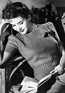 The pattern was published during the 1940s. It is a puffed, short sleeve sweater with a square neckline and ribbing from the waist down.