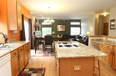 Gourmet island kitchen opens to step-down family room.  Granite counters, oak flooring, and raised panel oak cabinets.