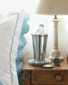 Give your overnight guests the five-star treatment by setting chilled spring water on their nightstand. Choose a vessel, such as a vase or a large julep cup, that is deep enough to accommodate a small bottle and ice. Place a saucer underneath to collect the condensation and protect the surface of the table.