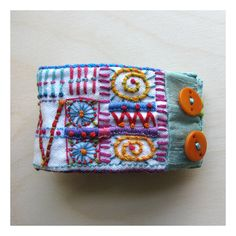 Hand-stitched cuff with vintage detailing from Madrigal Embroidery
