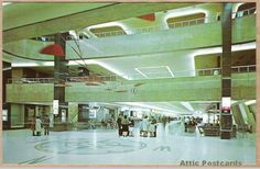 """Vintage postcard of an inside view of the Greater Pittsburgh Airport in Pittsburgh, Pennsylvania. Shows people, three levels, the compass directions on the floor and a mobile sculpture hanging from the ceiling. """"Color"""" by Carl Scholfield."""