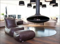 Impressive Hanging Fireplace for Modern Home: Minimalist Living Room With Black Hanging Fireplace And Comfy Relaxation Chair Minimalist Home Decor, Minimalist Interior, Minimalist Living, Hanging Fireplace, Suspended Fireplace, London Living Room, Freestanding Fireplace, Interior Minimalista, Italian Furniture