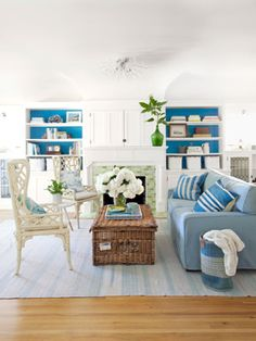 These bookcases, backed in vivid blues, contrast to the white cabinetry.