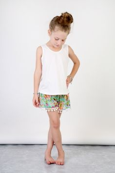 Our absolute best seller....softly shirred waist and loose leg trimmed with soft cotton pom pom's!  The fit of this short is so versatile due to the nature of the stretch waist and loose leg.  Please see sizing notes...available in a multitude of colours and most kids want them all!  Every little girl seems to adore her pompom shorts!Small - 2 - 3 also fits over nappy on a walking bub of approx 15mthsMedium - 4 - 6 Large - 6 - 9 however have sold to girls as old as 12yrs