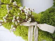 Make a Modern Color-Blocked Wreath and Dress It Up With Faux Berries >> http://blog.diynetwork.com/maderemade/how-to/how-to-make-an-ombre-pom-pom-wreath?soc=pinterest