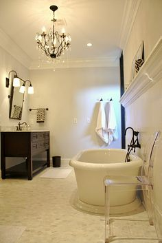 looklingerlove.blogspot.com  gorgeous, chic bathroom design with light gray walls, soaking tub, honed marble floor, Ghost chair, crystal chandelier, espresso stained bathroom cabinet vanity, oil rubbed bronze pivot mirror & sconces and beadboard paneling.