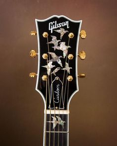 Gibson Custom Doves in Flight Brazilian Rosewood Acoustic Guitar!  That's cool as. I would like mother of pear seagulls on the neck and on the head like this.