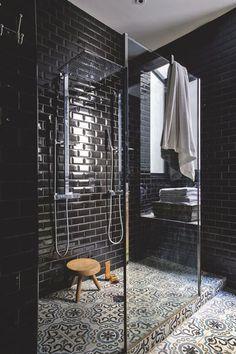 """La douche habillée de carreaux de métro noirs fait ressortir les motifs des carreaux de ciment au sol, Carrelages du Marais, tabouret """"Berger"""" de Charlotte Perriand, réédité par Cassina"""