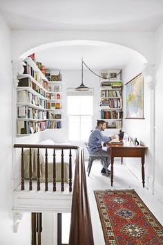 built-in bookshelves, narrow table, couch or chaise and pendant transform large landing into reading/office area