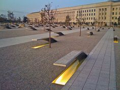 Pentagon Memorial in Arlington, VA commemorates the 184 lives lost in the Pentagon and on American Airlines Flight 77 during the terrorist attacks on Sept. 11, 2001. The memorial consists of two acres with 184 benches, each dedicated to an individual victim. Each bench is engraved with an individual's name and extends over a pool of water that glows with light at night. They are organized by a timeline based on the ages of the individuals.