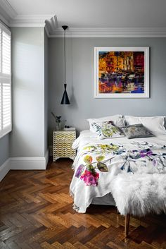 Bedroom inspiration. Soft grey walls, a flowery bedspread and a gorgeous parquet wood floor.