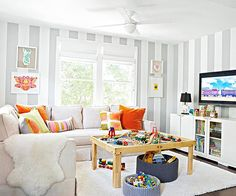 Fun kids' play room. Love the mix of patterns, striped walls, and simple artwork.