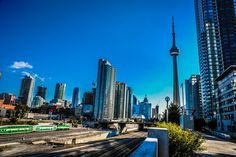 This photograph is what you think of when you think of Toronto, Ontario, Canada. The photograph shows tall highrise condos and commercial buildings, the transit system with a GO train on it and the CN Tower. There is still green (nature) in downtown Toronto and a lot of areas where you can view the skyline. #Toronto #Ontario #Canada #travel #tourism #CNTower #architecture #photography #photo #photos