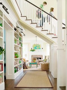 "Great use of the ""wasted"" space under stairs.  Love the white and dark trim together and the bookcases and the pops of color!"