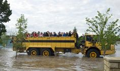 Residents are evacuated in a large truck from downtown High River in Alberta province