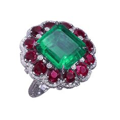 EMERALD, RUBY & DIAMOND RING With an octagonal Colombian emerald (minor) 11.35cts surrounded by rubies 5.80cts and diamonds 1.57cts. Mounted in platinum and gold.