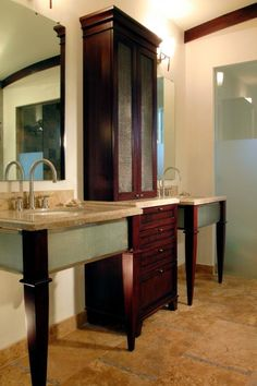 Sleek vanities in custom finishes make this smaller-scale master bath feel larger. The room required more storage, so designer Bea Pila placed a tower cabinet between the two sinks. With its combination of adjustable enclosed shelves on top and pullout drawers below, the furniture-like tower offers a place for everything.
