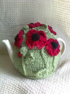 Poppy Tea Cosy. Maybe I could adapt this; knit plain cosy and lid, crochet flowers in 2 pieces so the heads can embellish the lid whilst stems are on cosy.