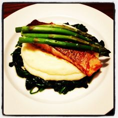 Salmon with asparagus on a bed of creamy mash with wilted spinach