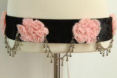 CINTURÓN ROSAS GASA -  Terciopelo negro, rosas de gasa, cadenas de metal con pequeñas cascabeles. Se ata con cinta de raso rosa. Medida cinturón: 79 cm.  Medida total cinta: 2 m.  Precio: 25 €