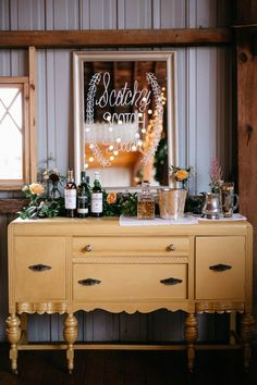 Lush greenery garland, a DIY hand-lettered mirror sign, and classic scotch accoutrements create a gorgeous self-serve bar | Image by Dan Stewart Photography