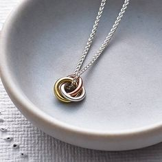 A beautiful handmade silver pendant or three coloured gold ring pendant, on a fine silver chain or gold chain.The pendant can be ordered in both all silver and all gold in a high polish finish and comes as standard on a fine silver chain. Alternatively you can also choose from a 9ct yellow or rose gold chain.'A circle is an endless line, no beginning no end, symbolising eternity.' This silver or tri-colour gold ring necklace on a fine chain is handmade by Jessica and is a beautiful gift for…