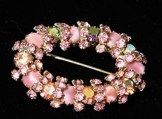 ITEM # 101638  Mid century, circa 1960s pink art glass and pink glass rhinestone Aurora Borealis brooch in an oval shape. There are 7 pink faceted glass AB rhinestones, 7 pink art glass cabochons, and 56 small pink faceted glass accent rhinestones for a total of 70 rhinestones, all hand prong set, in a gold tone metal, possibly gold plated.  Brooch measures 2 by 1/2.  Very good vintage condition with typical wear due to age and handling. No missing rhinestones or faux pearls. The AB finish…