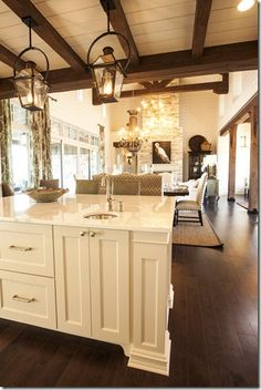 light cabinets, dark floors, wood beams, stone fireplace, open kitchen/living room