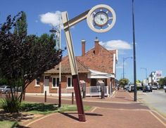 A two-faced Town Clock suspended from a pillar in the rural centre of Pinjarra.