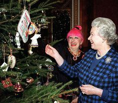 The Queen and fashion designer Zandra Rhodes admire decorations on a Christmas tree in the Picture Gallery at Buckingham Palace, 15 December 1998. Some 500 ornaments crafted by celebrity and amateur embroiderers were made for the tree.