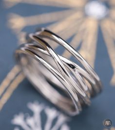 This sleek platinum wedding ring is designed to look like intertwined strands of metal. The piece is wide, and makes a beautiful statement, but the thin strands make the whole design very light. And on the inside of each strand, a personal inscription makes this ring really meaningful to the bride-to-be who will wear it.