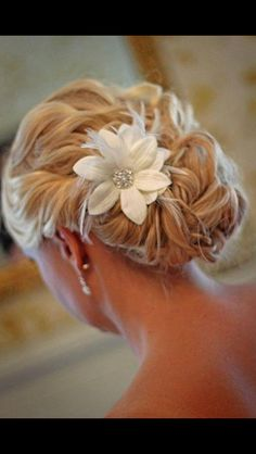 Simple hairdo, pinned with a white flower.